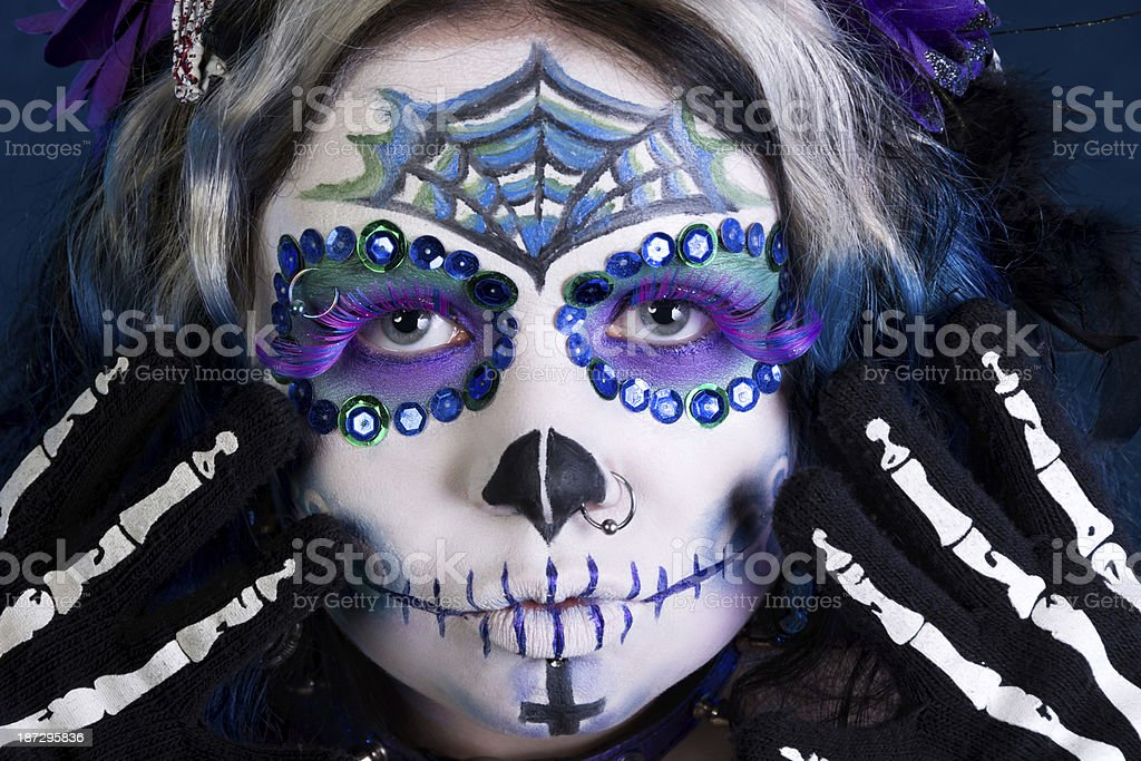 Face with sugarskull makeup and skeleton gloves. stock photo