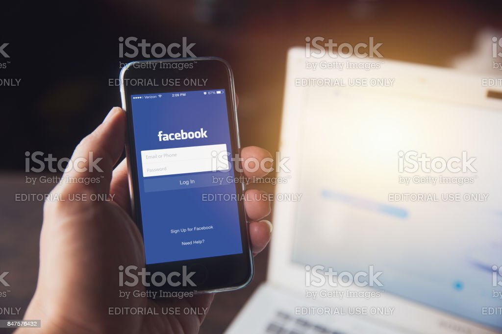 Facebook App on iPhone with computer laptop background closeup male hand hold social network on smart device concept. - Foto stock royalty-free di Abbigliamento elegante