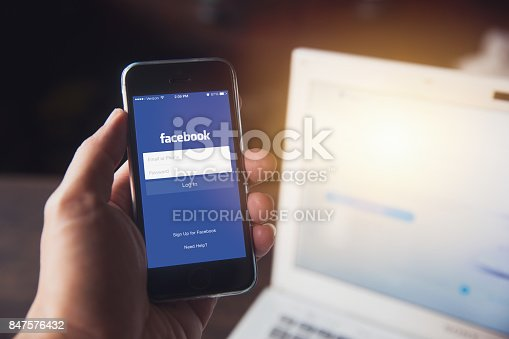istock Facebook App on iPhone with computer laptop background closeup male hand hold social network on smart device concept. 847576432