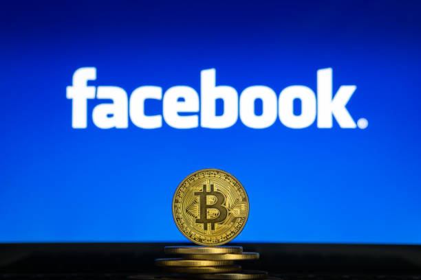 Facebook logo on a computer screen with a stack of Bitcoin cryptocurency coins. stock photo