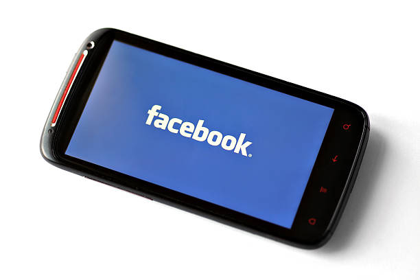 facebook logo on a smartphone screen - logo stock photos and pictures