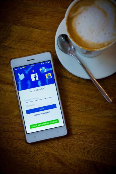 facebook-social-media-netzwerk auf smartphone- und kaffeezeit - www kaffee oder tee stock-fotos und bilder