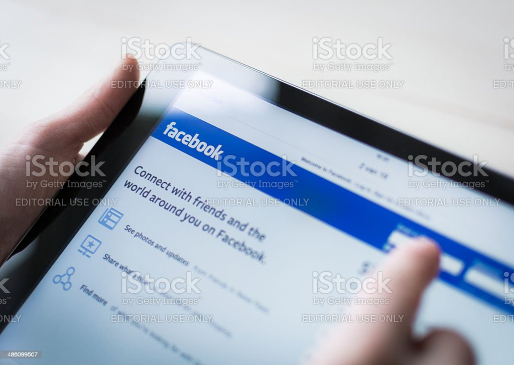 Facebook user on ipad stock photo