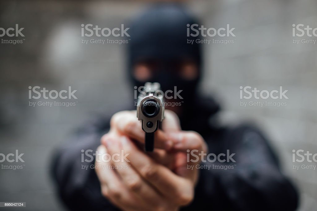 A face-covered man pointing a gun at lens stock photo