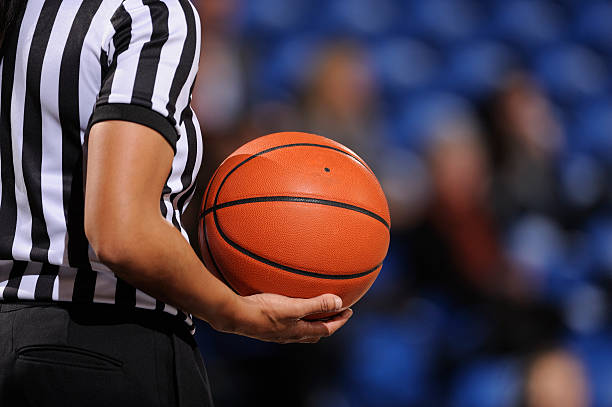 Faceless female basketball referee holds ball in one hand A basketball referee holds a ball during a game. referee stock pictures, royalty-free photos & images