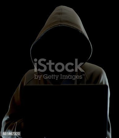 istock Faceless hooded hacker with laptop black background 531867320