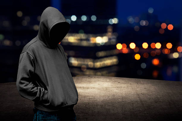 Faceless man in hood on the rooftop Faceless man in hood on the rooftop with city background at night time crime stock pictures, royalty-free photos & images