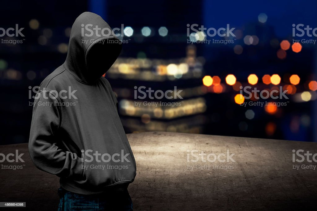 Faceless man in hood on the rooftop stock photo