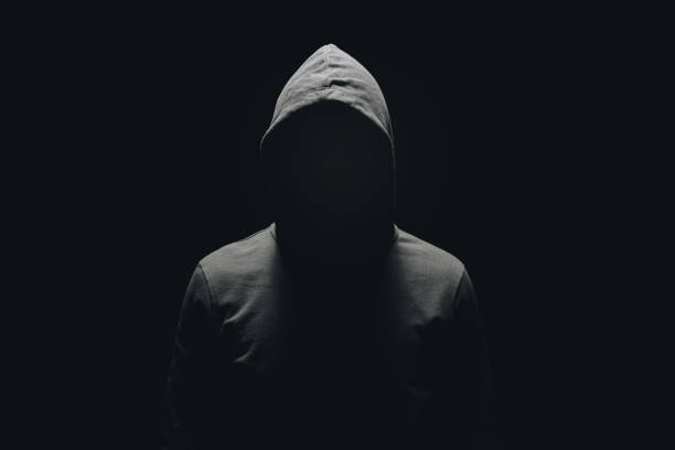 faceless man in hoodie standing isolated on black - thief stock photos and pictures