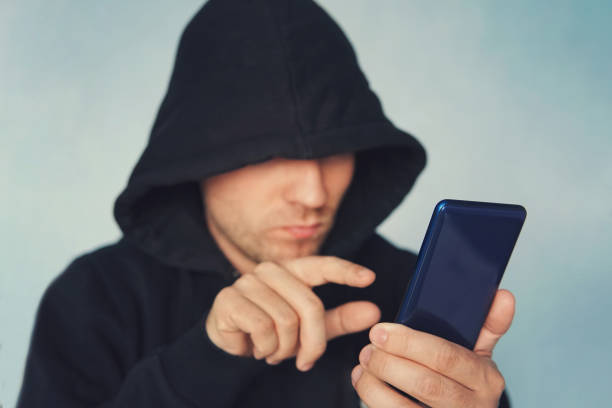 Faceless unrecognizable hooded person using mobile phone, identity theft and technology crime concept, selective focus on body, hacking a smartphone. identity theft. Faceless unrecognizable hooded person using mobile phone, identity theft and technology crime concept, selective focus on body, hacking a smartphone. identity theft. alias stock pictures, royalty-free photos & images