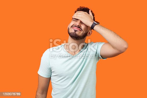 Facepalm. Portrait of desperate brunette man with beard in white t-shirt covering face with hand, feeling sorry and blaming himself for the mistake. indoor studio shot isolated on orange background