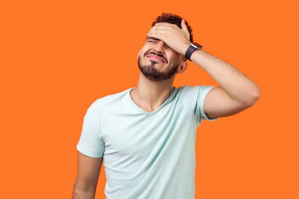 facepalm. porträt von verzweifelten brünetten mann bedeckt gesicht mit derhand. indoor-studio-aufnahme isoliert auf orangefarbenem hintergrund - bedauern stock-fotos und bilder