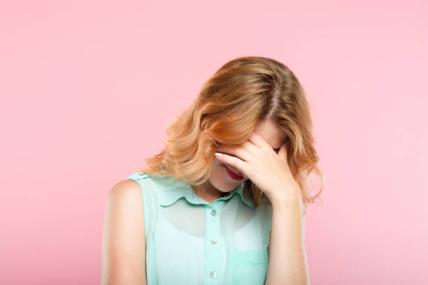 facepalm shame embarrassment girl cover face facepalm embarrassment and shame emotion. ashamed smiling girl covering her face with a hand. young beautiful woman portrait on pink background. head in hands stock pictures, royalty-free photos & images