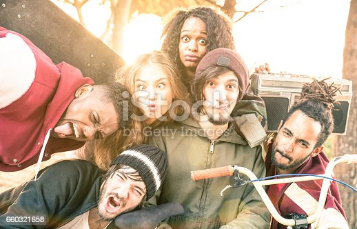 istock Faces of best friends taking selfie at bmx skate park contest - Happy youth and friendship concept with young multiracial people having fun together in urban city area - Bright warm desaturated filter 660321658