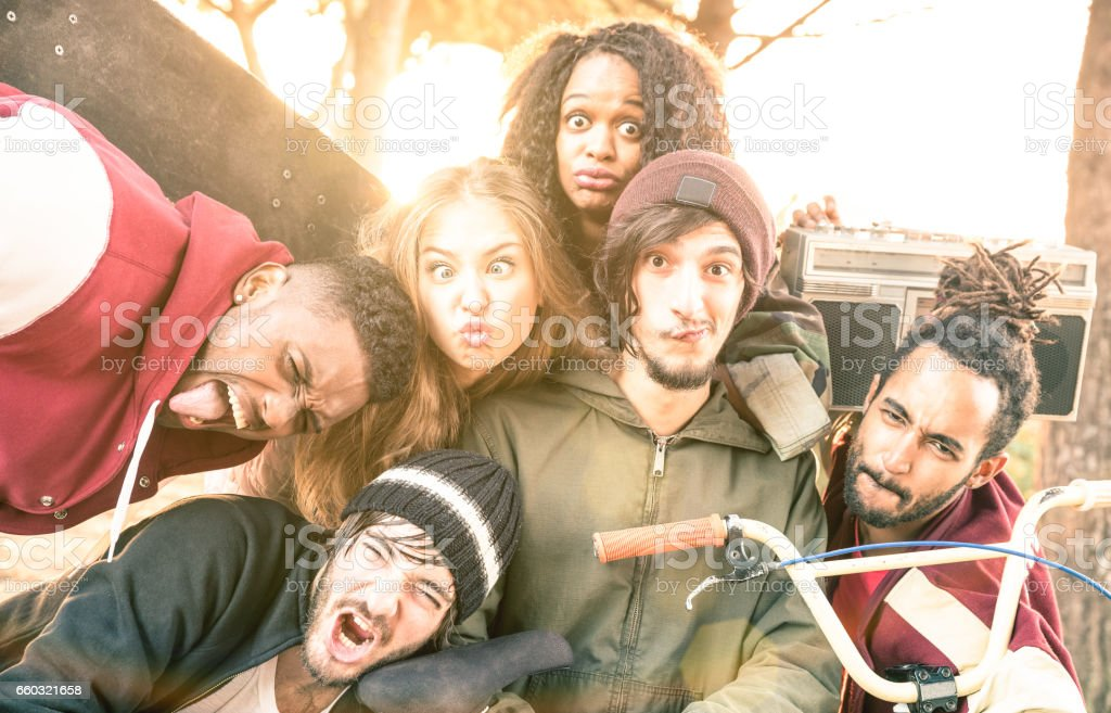 Faces of best friends taking selfie at bmx skate park contest - Happy youth and friendship concept with young multiracial people having fun together in urban city area - Bright warm desaturated filter stock photo