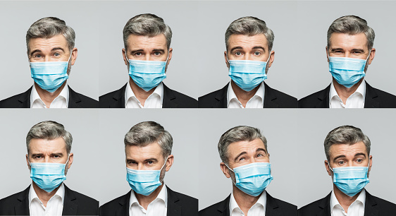 Eight different faces of mature businessman wearing N95 face mask, composite images. Studio shot, grey background.