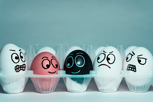istock Faces on eggs in the form of facial expressions, reflecting emotions. The concept of racism, misunderstanding, a barrier in relations, denial of society. Barriers between people, prejudice. 903685874