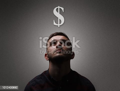 Facet portrait a man looking up on dollar money symbol. Dark lighting portrait bristle men in checkered shirt looks up with his head up on a dark gray background copy space