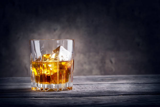 Faceted glass of whiskey with ice Faceted glass of whiskey with ice on dark background brandy stock pictures, royalty-free photos & images