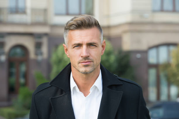 Facial care and ageing. Beauty of mature face. Traits and behaviors that make men more appealing. Attractive mature man. Mature guy with grey hair and bristle. Men get more attractive with age stock photo
