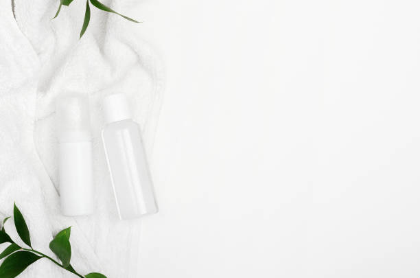 Facial care cosmetic products in bottles top view. Micellar water container mockup on white towel with green leaves background. Fluid makeup remover, face skin lotion with natural ingredients flat lay stock photo