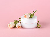 istock Facial cream and small roses of light peach color on a pastel pink background. Cosmetics for moisturizing and cleansing. Skin, hair or body care. 1248448978