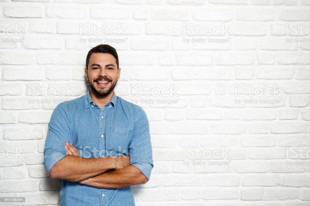 Facial Expressions Of Young Beard Man On Brick Wall stock photo