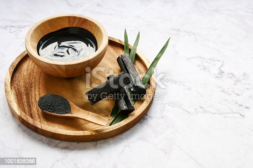 istock Facial mask and scrub by activated charcoal powder on marble table 1001838386
