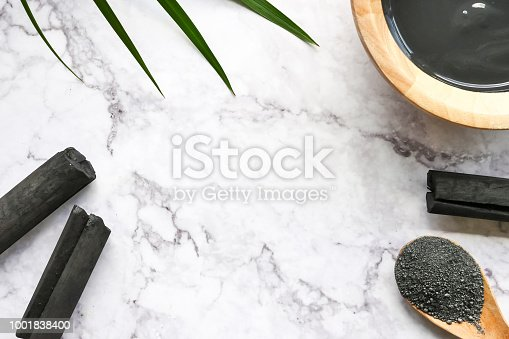 istock Facial mask and scrub by activated charcoal powder on marble table. Free space for text 1001838400