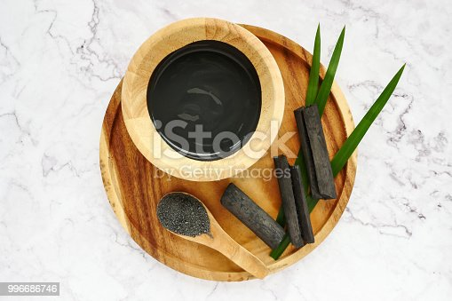 istock Facial mask and scrub by activated charcoal powder on marble table 996686746