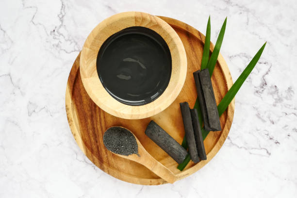 Facial mask and scrub by activated charcoal powder on marble table stock photo