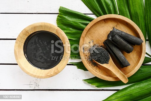 istock Facial mask and scrub by activated charcoal powder on wooden table 1001838392