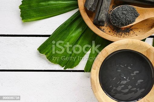 istock Facial mask and scrub by activated charcoal powder on wooden table 996686738