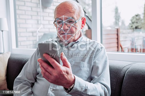 Senior man holds smart phone and it performs a scan of his face. Facial recognition software on the phone can unlock the screen and even pay for items online.