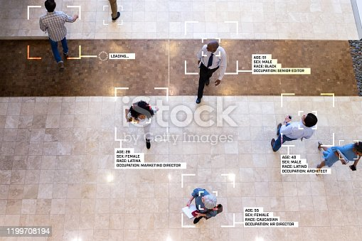 While walking through an office lobby, diverse group of business professionals are identified by facial recognition technology, The information includes personal as well as professional information.