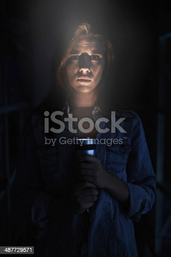 A young woman looking serious while holding her flashlight in the dark