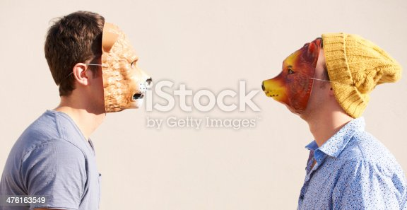 Two young hipsters facing off while wearing animal masks