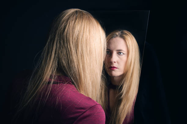 Facing Oneself A woman with an unfriendly expression faces herself in a mirror. low self esteem stock pictures, royalty-free photos & images