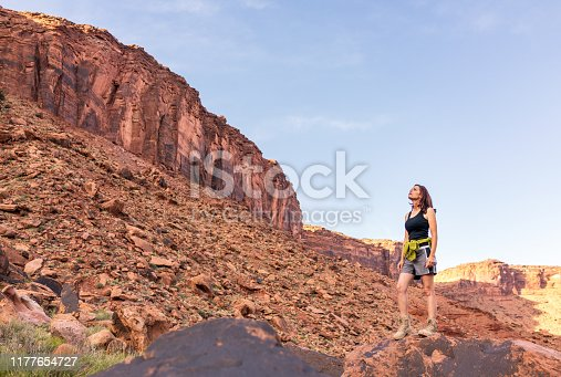 A woman looks up towards the ridge that she's hiking towards, near Moab in the southwestern Utah, USA,