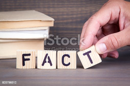 922107104istockphoto fact. Wooden letters on dark background 825796512
