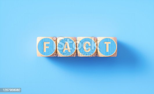 Fact written blue wood blocks sitting on blue background. Horizontal composition with copy space. Fact concept.