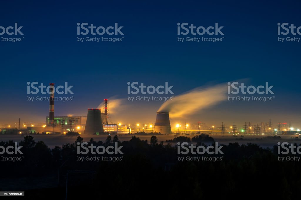 Factories at night, the silhouettes of the pipe producing a noxious smoke into the sky. stock photo