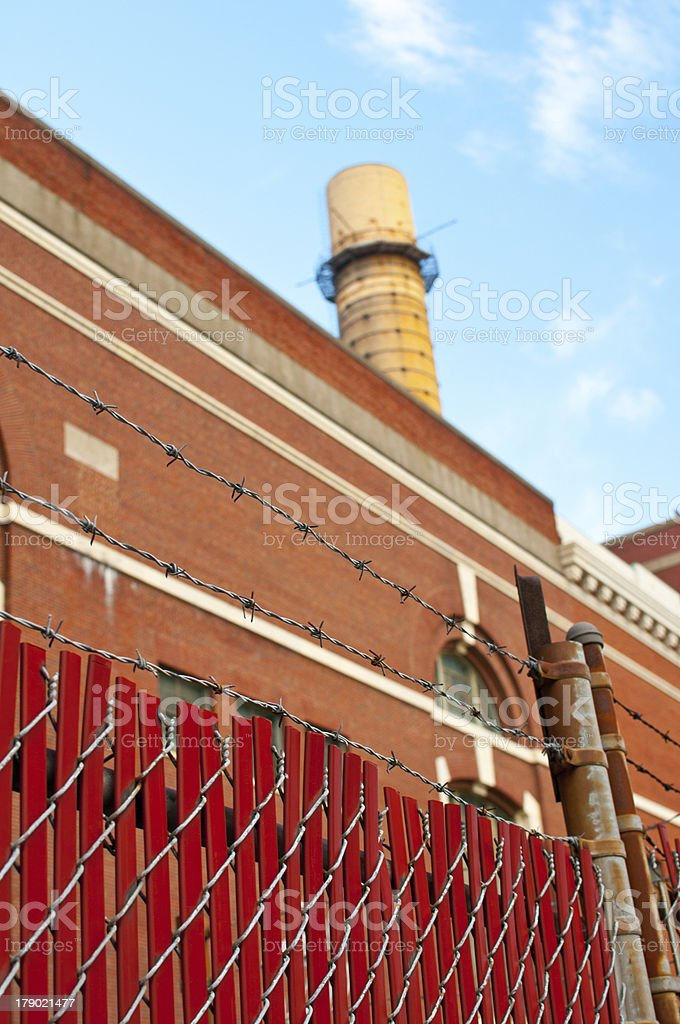 Factory chimney and fence with barbed wire royalty-free stock photo