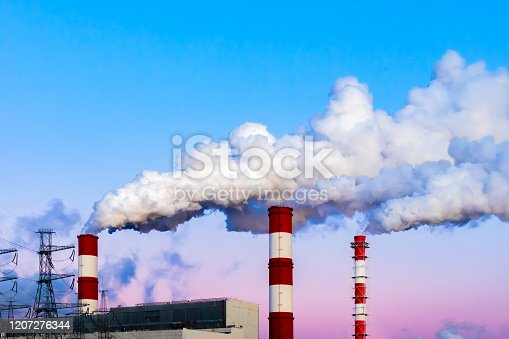 Factory chimneys pollute the air, thick dirty smoke, twilight evening sky. Beautiful industrial landscape, environmental pollution, poisoned air