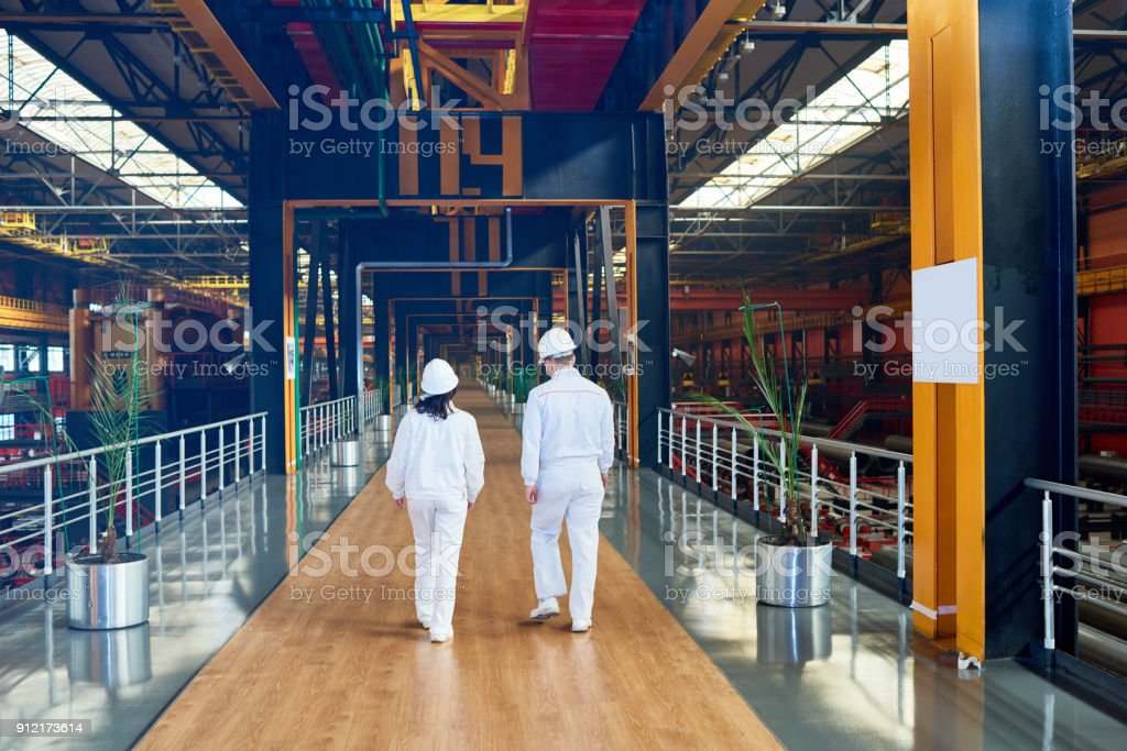 Factory employees in uniform moving along bridge stock photo
