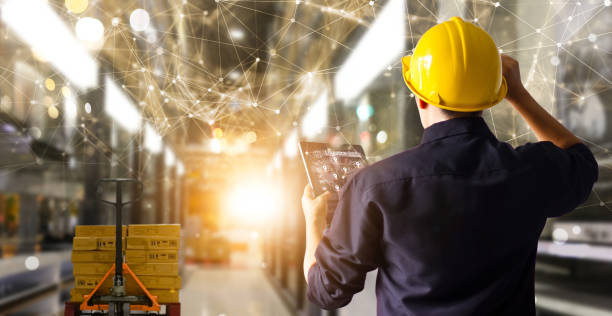 Factory engineer hold tablet manage inventory control and delivery smart transportation through intelligent warehouse management system.Global logistic contribution and industrial innovative. stock photo