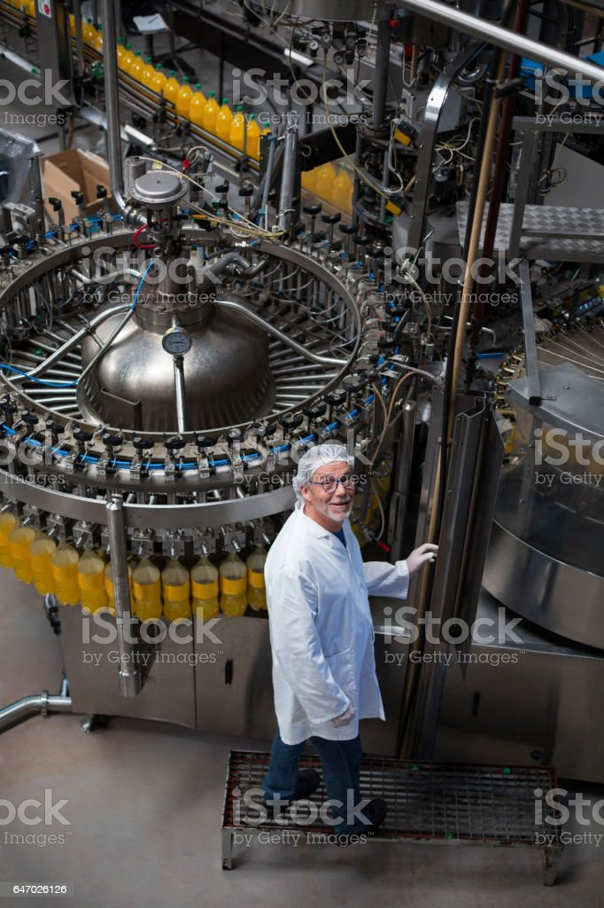 Factory engineer monitoring filled juice bottle on production line stock photo