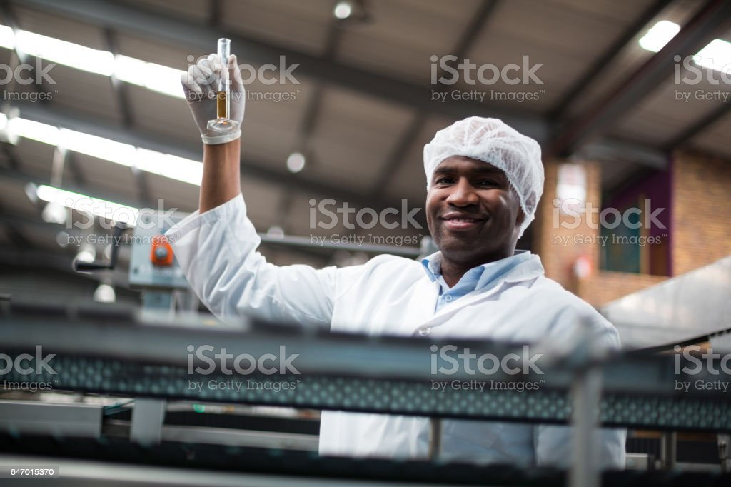 Factory engineers holding a sample of drink stock photo