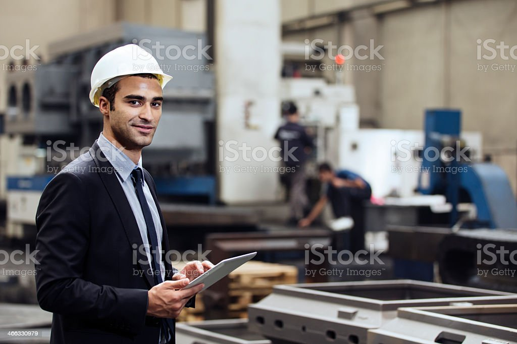 Factory manager holding tablet in factory stock photo