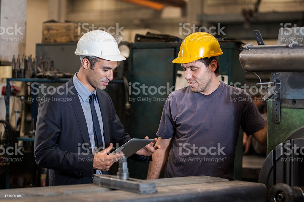 Factory manager talking to an operative in hard hat royalty-free stock photo